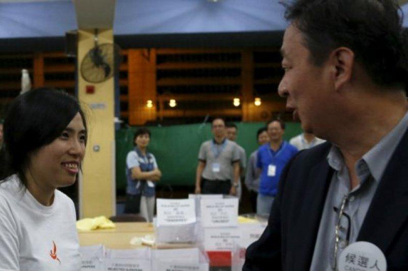 這次選舉「政治素人」有所突破。「青年新政」成員鄺葆賢(圖左)與競爭者資深區議員劉偉榮(圖右)握手。(BBC中文網)