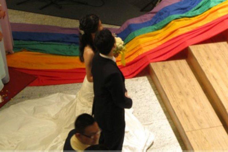 新郎新娘接受福證的時候,地上鋪著的是教會中頗為敏感的同志彩虹旗(BBC中文網)