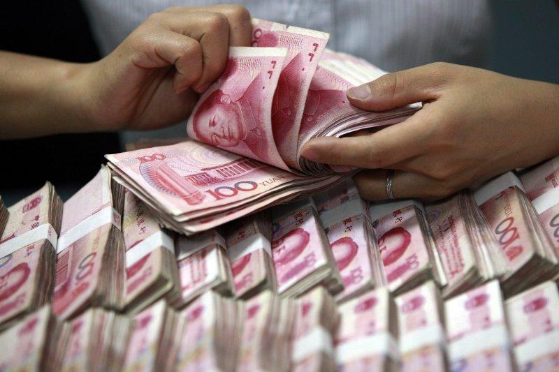 中國人民銀行11日調降人民幣兌美元中間價0.1%,至人民幣6.4140元兌1美元。(美聯社)