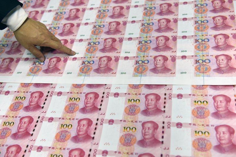 北鈔公司工作人員在抽查新版百元鈔票凹印效果(新華社)