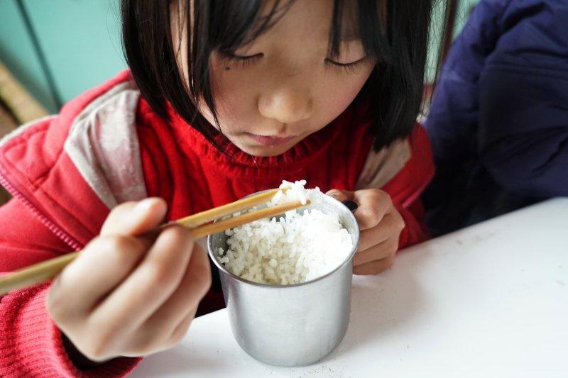 在江西省修水縣大椿鄉柏樹村小學,學生楊欣在吃自帶的午飯。由於家庭條件差,她的午飯除了米飯什麼也沒有(新華社)