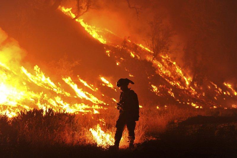 加州今年8月又發生森林野火,一名消防員就在驚人的大火前查看狀況。(美聯社)
