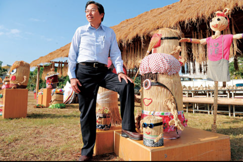 草屯鎮長洪國浩擅長活化資產,很難想像其身後陳設著稻草裝置藝術的植物公園,前身竟是一片已禁葬且髒亂的墓地。(程思迪攝)