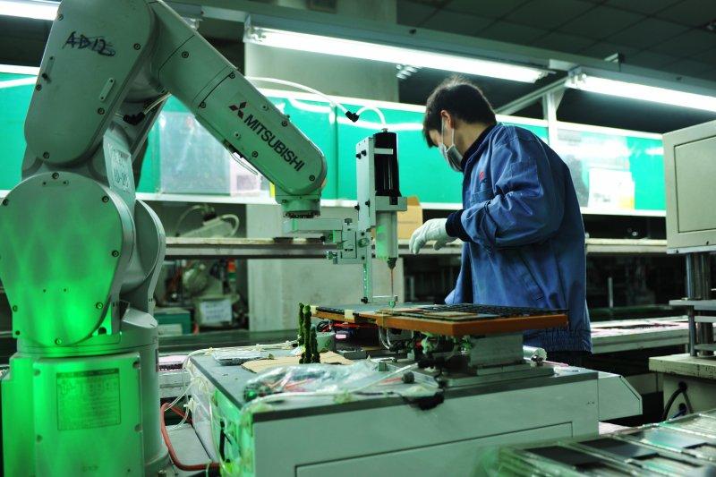 昆山製造業台企加快轉型,機械手操作筆記型電腦外殼點膠製成工序(新華社)