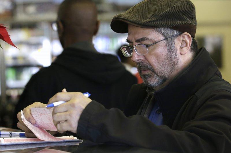 加州沙加緬度的一位民眾正聚精會神挑選威力球的號碼。(美聯社)