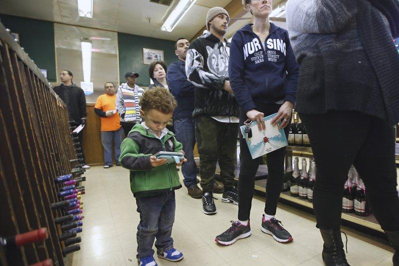 加州沙加緬度的一位小朋友專心地打電動,絲毫不理會大人們追逐彩金的排隊行為。(美聯社)