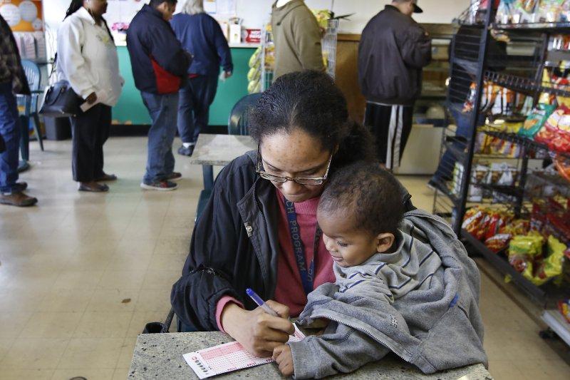 加州一位母親抱著仍在襁褓中的孩子,滿懷希望地劃下彩券。(美聯社)