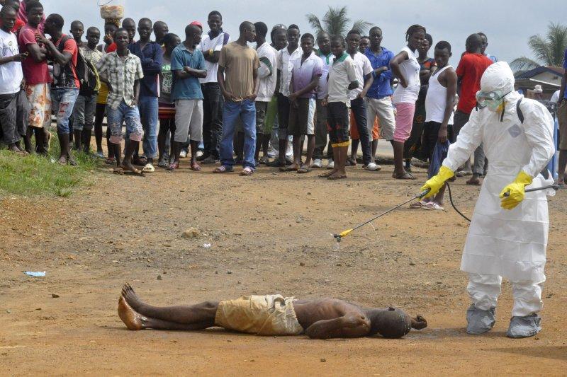 賴比瑞亞的公衛人員對伊波拉死者遺體進行消毒(美聯社)