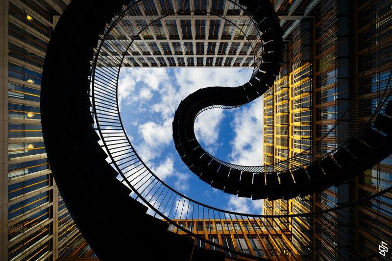 """Stairs to sky 。""""原本樓梯是為了前往更高的地方所發明,而這種無限的追求直指天際"""" Umschreibung(Rewriting)2004完成於慕尼黑的公共藝術作品,對比於周遭方正的辦公室建築,這一座如迴圈一般的無限樓梯,是訴說著人們對自我的追求。(2015法國PX3國際攝影獎 建築類銀獎)"""