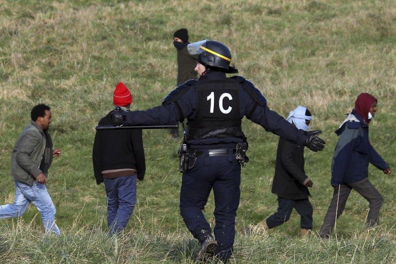 一名警察於21日要求移民離開加萊英法海底隧道周圍地區(美聯社)