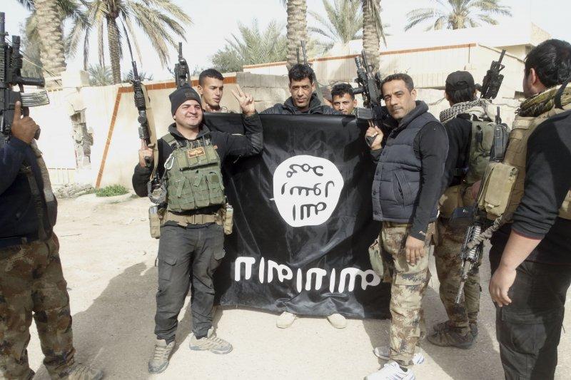 伊拉克軍隊展示尋獲的伊斯蘭國國旗。(美聯社)