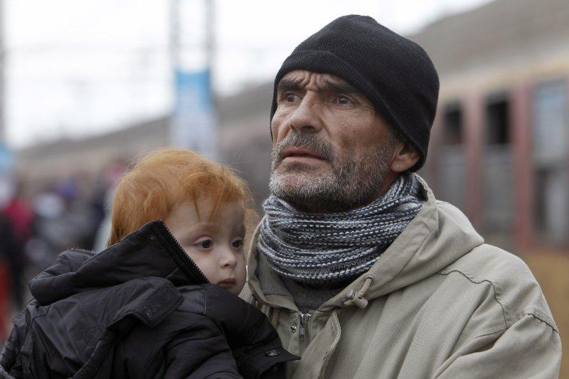 剛抵達馬其頓的難民爸爸手中抱著孩子,望向遠方(美聯社)