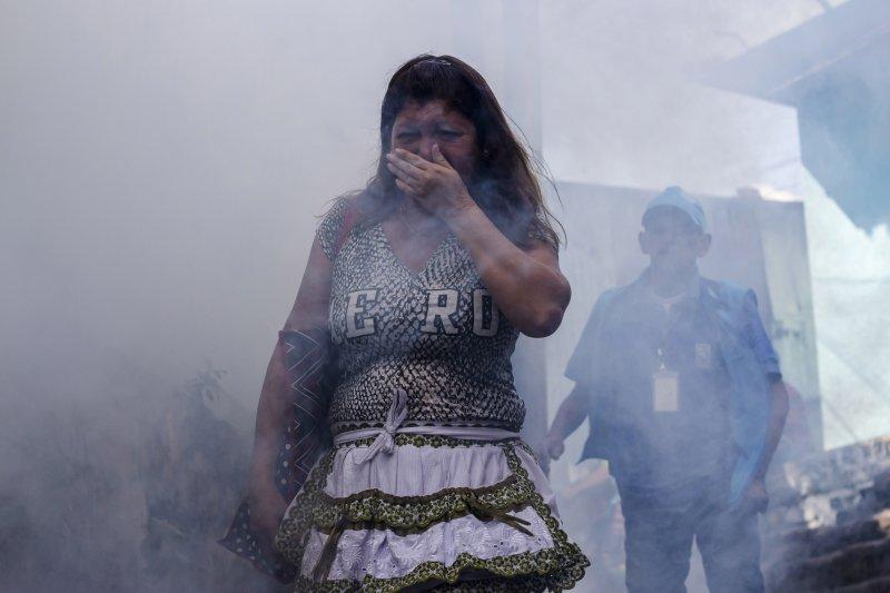 在薩爾瓦多的首都聖薩爾瓦多,公衛人員大量噴灑殺蟲劑,一名婦女掩面而過(美聯社)