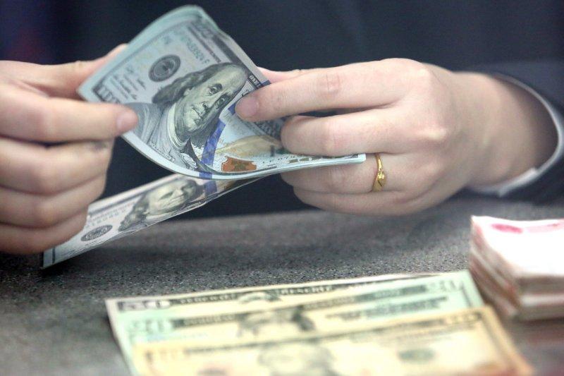 山東省臨沂市郯城縣一家銀行工作人員在清點美元(新華社)