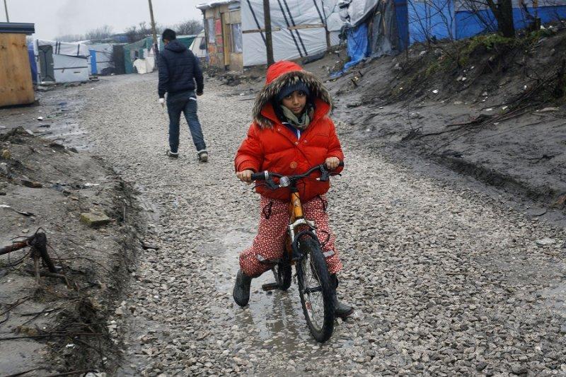 一名移民孩童於加萊難民營外騎著腳踏車(美聯社)