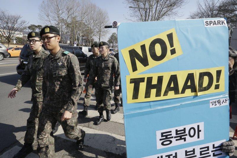 南韓民眾在國防部外抗議美軍打算部署「戰區高空防禦系統」(THAAD),剛好一隊士兵在示威人群前走過。(美聯社)