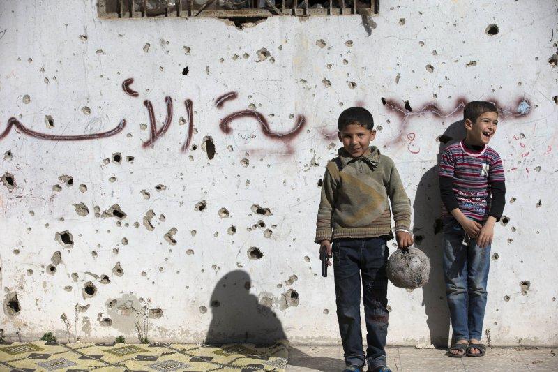 敘利亞男孩左手拿足球、右手拿玩具槍,站在寫著「敘利亞阿塞德」塗鴉、布滿彈孔一面牆之前。敘利亞幾乎毀於戰火,但孩子臉上還有笑容,就有希望。(美聯社)