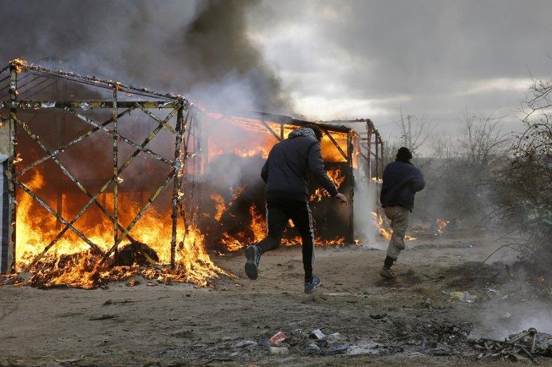 加萊移民跑經燃燒中的搭建屋(美聯社)