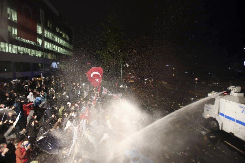 《時代報》遭政府接管,警方以強力水柱攻擊抗議民眾。(美聯社)