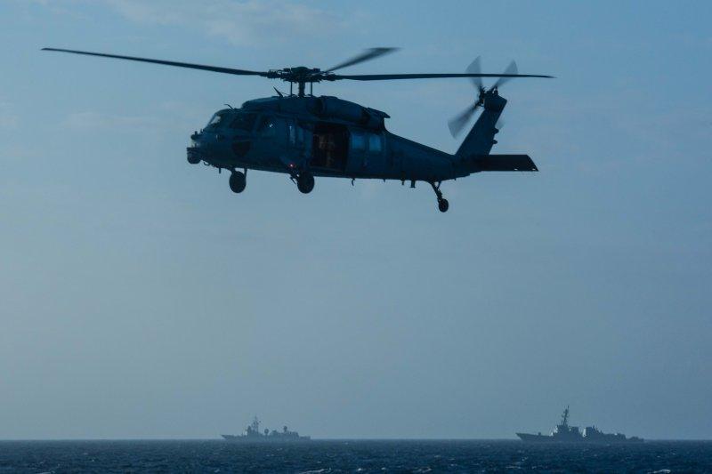 在美國海軍4日釋出的照片中,除了畫面中的美軍MH-60S海鷹直升機之外,遠處還可以見到中國海軍的船艦在附近監視美軍艦隊。(美國海軍官網)
