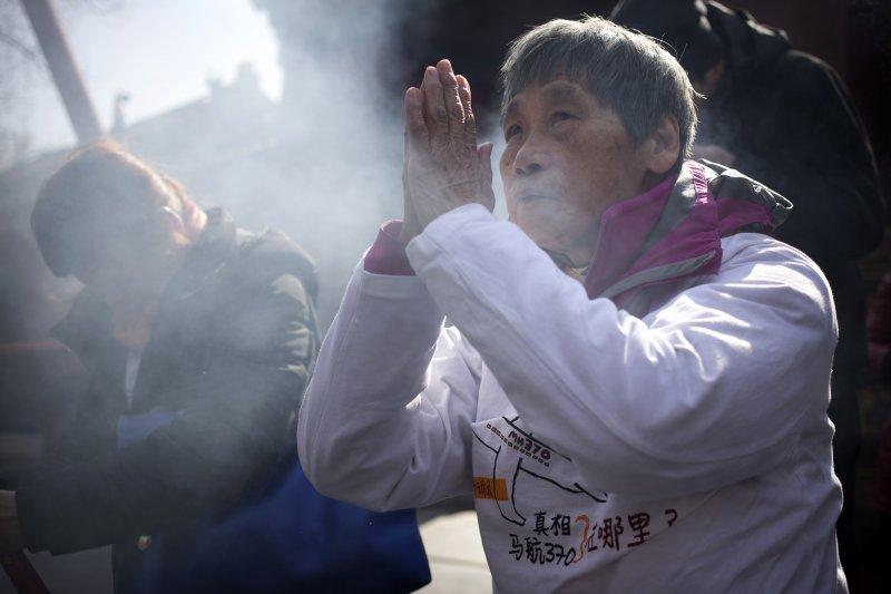 MH370失蹤乘客的家屬,8日在北京的寺廟裡為親人祈福、希望老天爺保佑他們能快點被找到。(美聯社)
