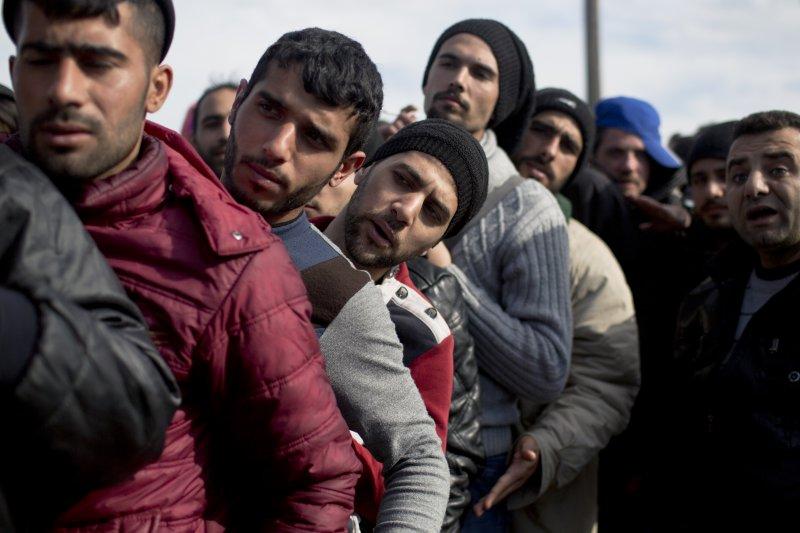 難民在希臘的難民營排隊,等待更正入境申請文件(美聯社)