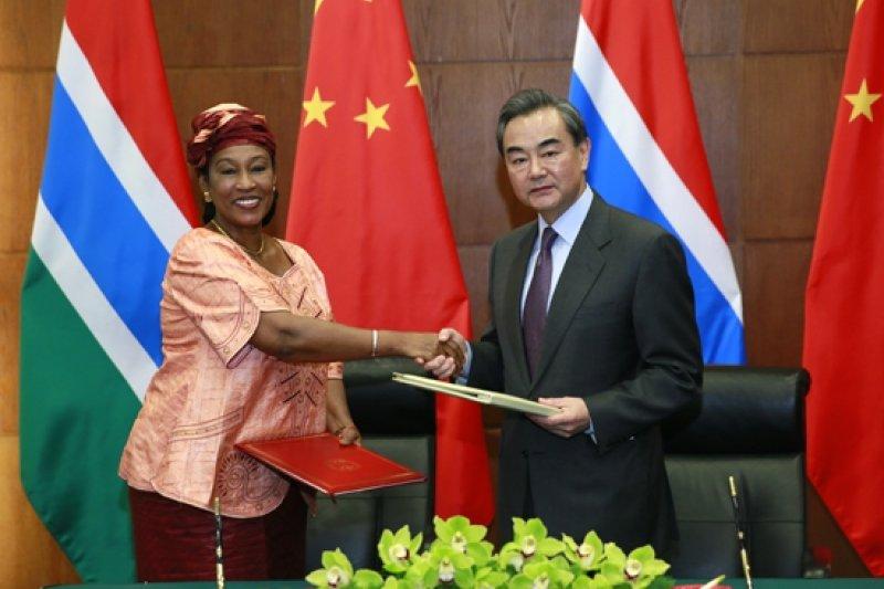 中國外交部長王毅(右)與甘比亞外交部長蓋伊握手,慶祝兩國建交。(取自中國外交部官網)