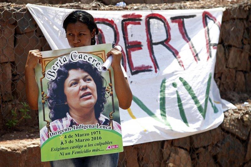 一名婦女在抗議中舉著環保領袖卡瑟雷斯的海報(美聯社)