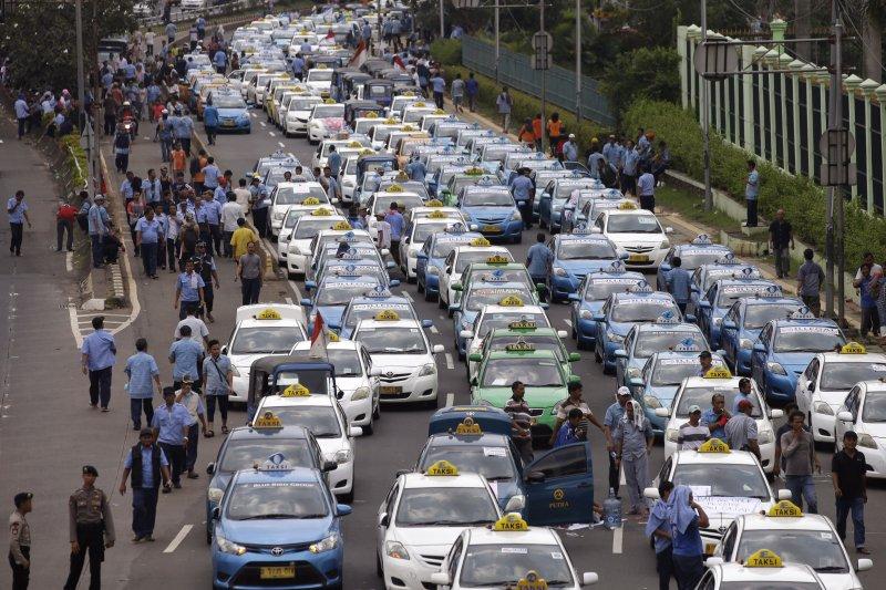 印尼的計程車司機22日在雅加達街頭抗議,強調Uber與Grab等叫車軟體完全非法。(美聯社)
