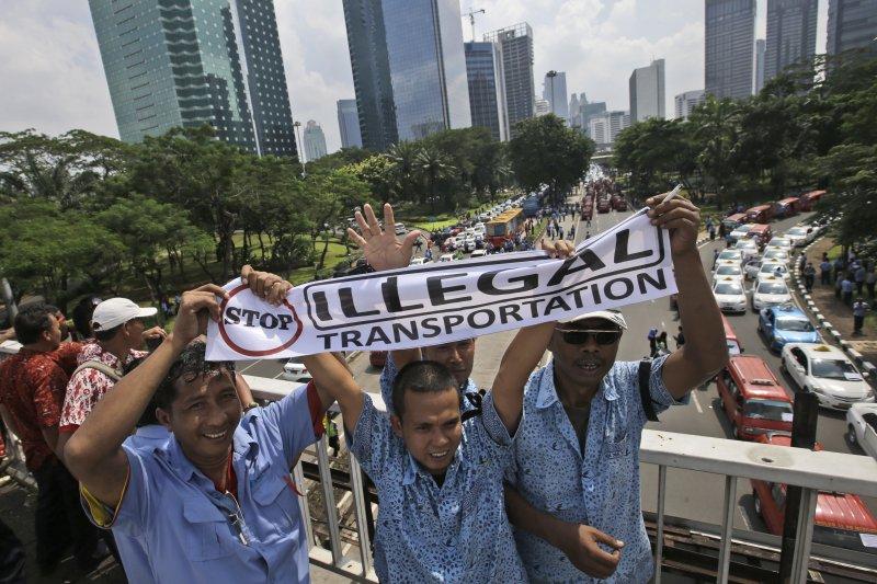 印尼的計程車司機22日在雅加達街頭抗議,反對Uber與Grab等叫車軟體。(美聯社)