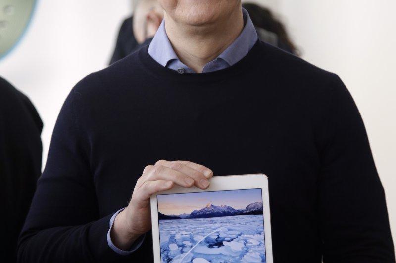 蘋果新產品越來越貴,不少果粉可能經濟上會「追趕不及」,圖為庫克展示新一代的iPad。(美聯社)