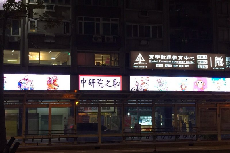 台北市大安區大安捷運站旁有民眾購買電子看板當「對聯」,以「中研院之恥」諷刺翁啟惠。(讀者提供)