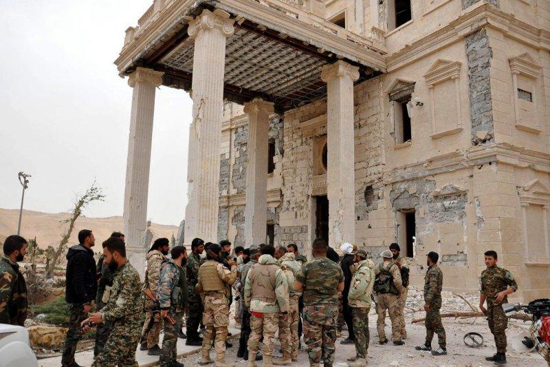 敘利亞政府軍攻進帕米拉古城後,在當地一座受損嚴重的宮殿外聚集整隊。(美聯社)