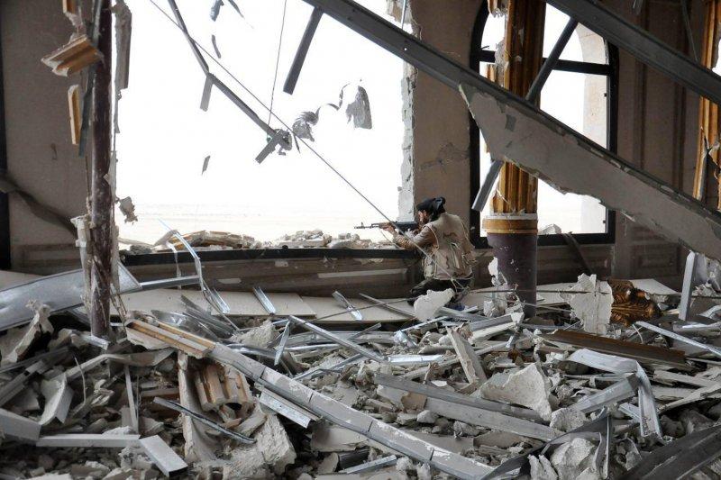 一名敘利亞政府軍在帕米拉一座受損嚴重的宮殿窗口,搜索外頭的敵軍身影。(美聯社)