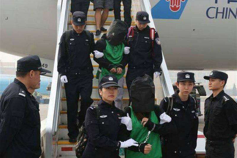 印尼破獲電信詐騙集團,其中有11名台灣人,印尼同意遣返回台。圖為肯亞詐騙案中中國強擄45名台灣人事件,第二批37名台灣人及中國嫌犯遣返抵達北京機場時,涉案嫌犯皆被戴上黑色頭套。(新華社)