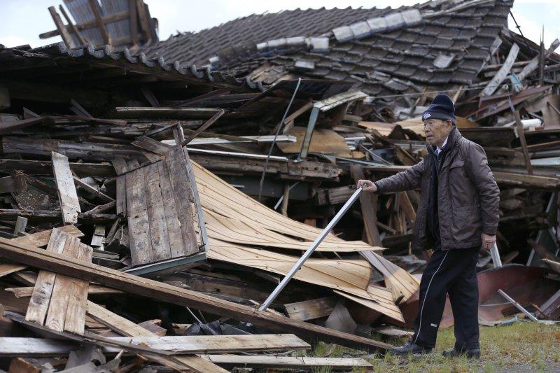日本一名長者經過倒塌房舍前。(美聯社)