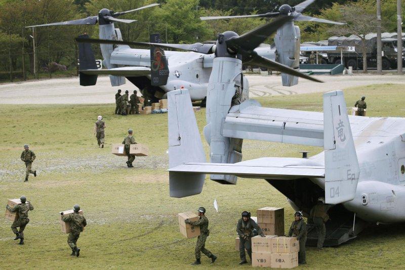 駐日美軍以MV-22魚鷹(Osprey)運輸機送來民生及救援物資,日本的自衛隊員忙著幫忙搬運。(美聯社)