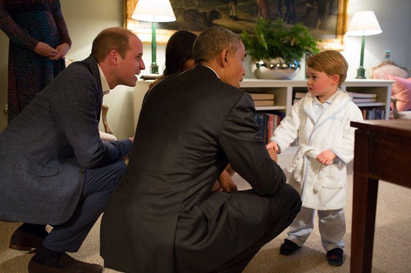 歐巴馬與威廉王子一起蹲下來與喬治小王子聊天。(美聯社)