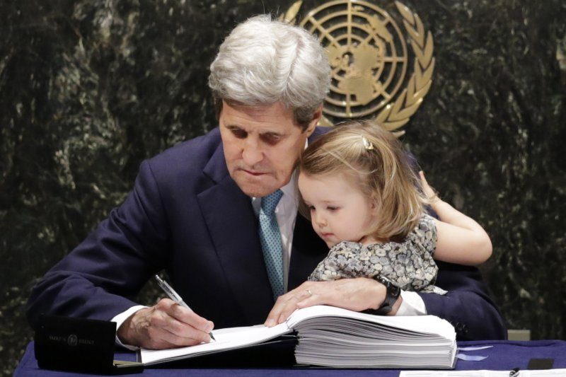 美國國務卿凱瑞(John Kerry)22日抱著孫女伊莎貝爾簽署《巴黎協定》(美聯社)