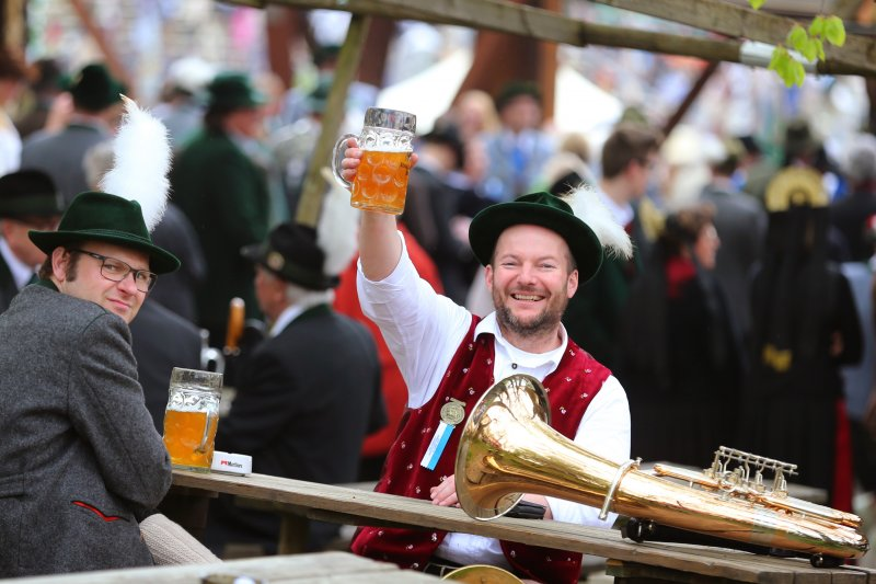 一身南德傳統打扮的德國民眾高舉酒杯。(美聯社)