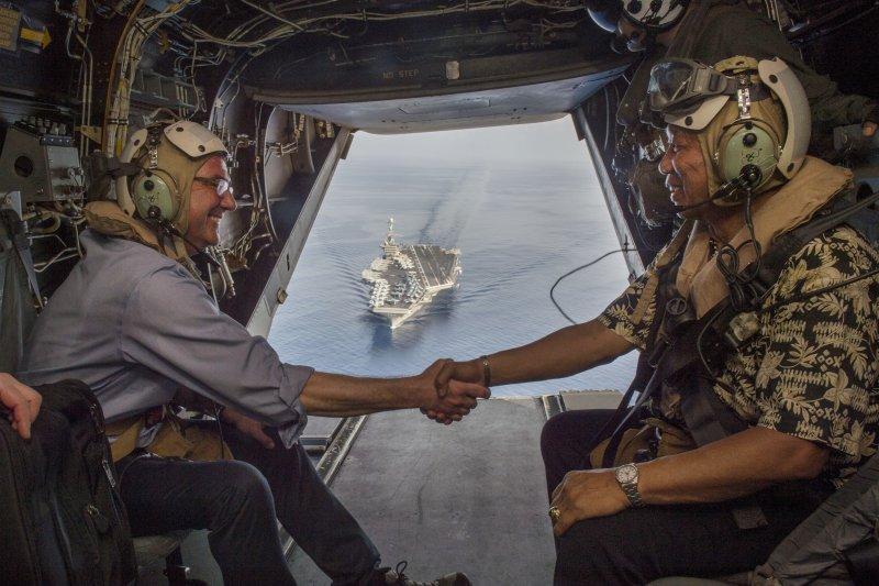 美國防長卡特與菲國防長卡茲敏在V-22魚鷹運輸機上握手,打開的艙門可以看見正在南海巡弋的史坦尼斯號航空母艦。(美國海軍官網)