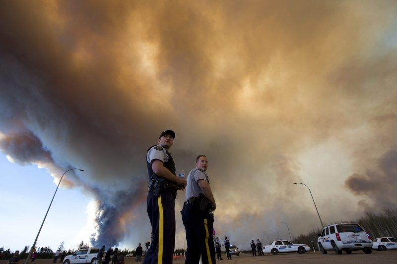 加拿大警方在麥克默里堡的漫天濃煙下指揮交通,疏散逃難民眾。(美聯社)