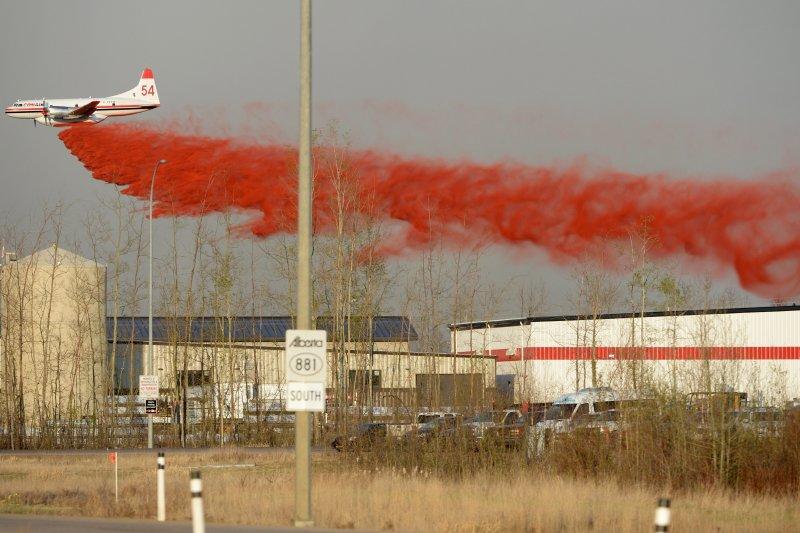 飛機在麥克默里堡上空噴散助燃劑,希望能減緩火勢延燒。(美聯社)