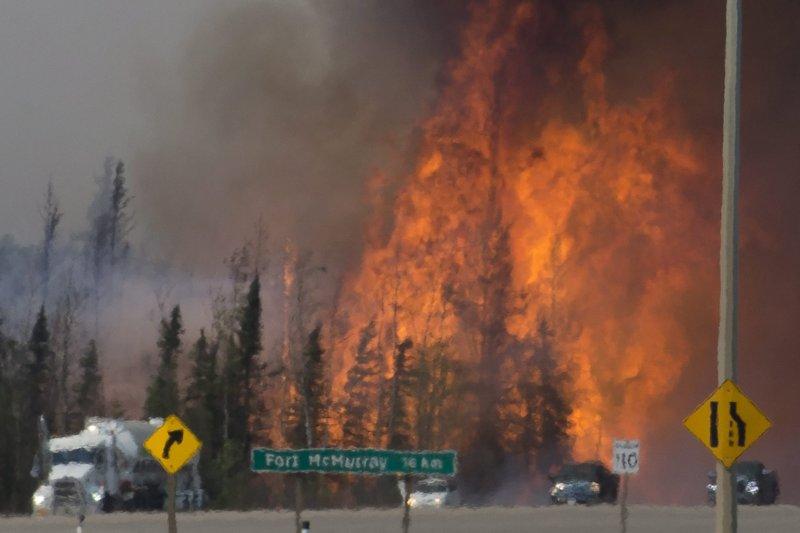 距離麥克默里堡16公里處的63號高速公路,逃難的車輛就在大火旁行駛。(美聯社)