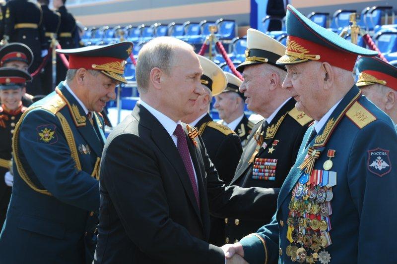 俄國總統普京與國防部長紹伊古(Sergei Shoigu)在紅場向曾參與衛國戰爭的老兵致意。(美聯社)