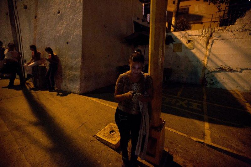 委內瑞拉不但食品藥品短缺,連電力都時有時無。首都卡拉卡斯郊區停電,民眾只能就著月光聊天。(美聯社)