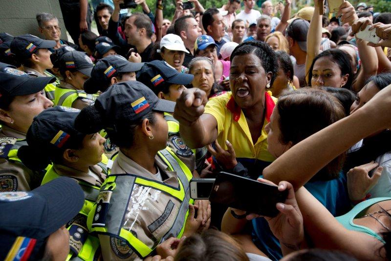 反對馬杜洛政府的民眾11日想遊行到國家選舉委員會抗議,但遭到警方阻擋,雙方大打出手。(美聯社)