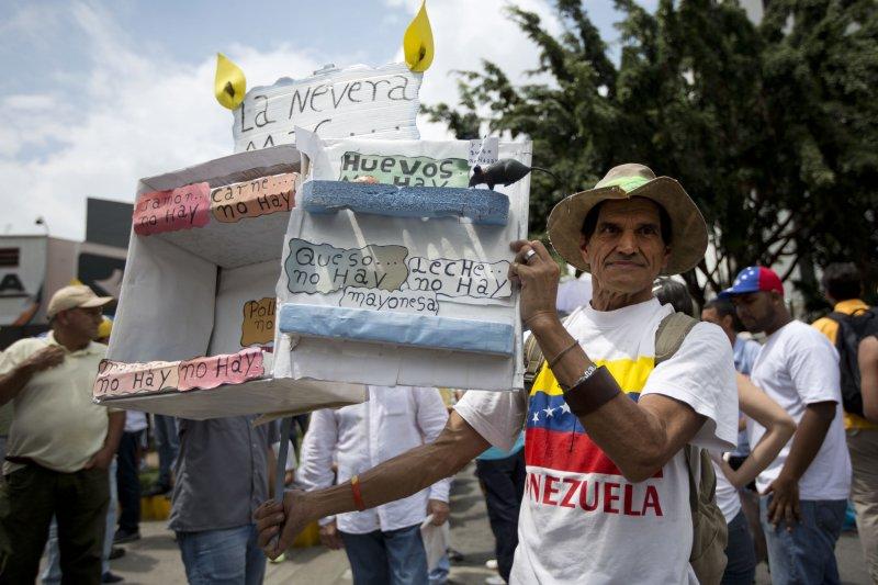 委內瑞拉示威民眾高舉空蕩蕩的紙紮冰箱,抗議民生物資奇缺(美聯社)
