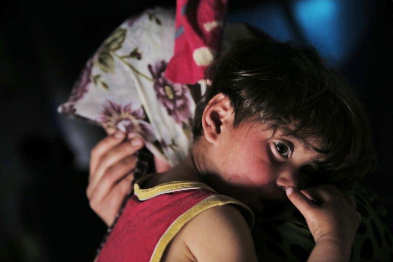 敘利亞難民2歲的瑪莉亞(Maria Sheikh)正被她的媽媽抱入懷中。他們是目前居住在土耳其千分之一的難民家庭,每個月一家五口靠世界糧食計劃署(World Food Program)的100元美金生活。