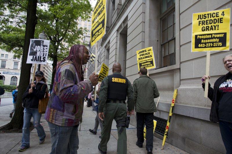 民眾12日在審理白人警官尼洛(Edward Nero)的法院外舉牌示威,希望為枉死的黑人青年葛瑞爭取正義。(美聯社)